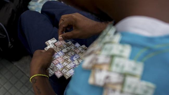 Saking tidak berartinya, warga Venezuela lebih memilih membuat uang kertas jadi kesenian. (AFP Photo/Federico Parra)