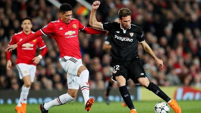 Bek Manchester United Chris Smalling mencoba menghentikan laju gelandang Sevilla Franco Vazquez. Tampil di Old Trafford, Setan Merah kalah agresif dari Los Sevilistas sejak babak pertama. (REUTERS/David Klein)