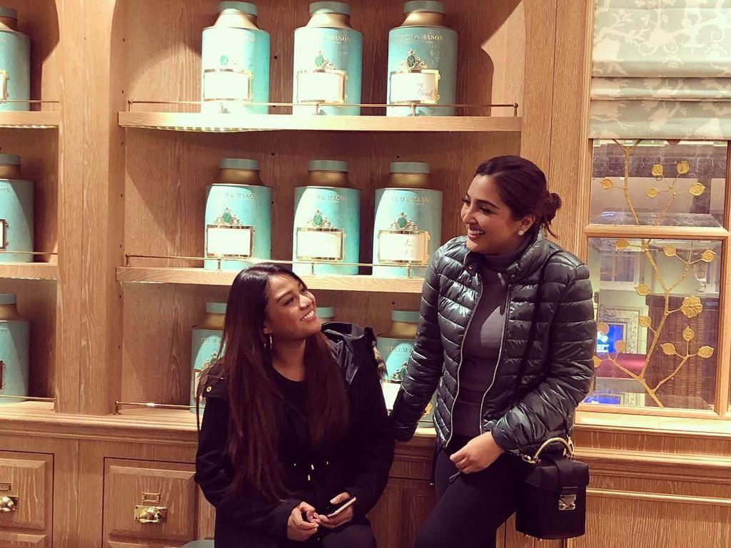 Di foto dengan gaya candid, Ashanty dan Aurel tampak gembira. Dengan latar aneka teko teh klasik yang cantik. Foto: Instagram @ashanty_ash