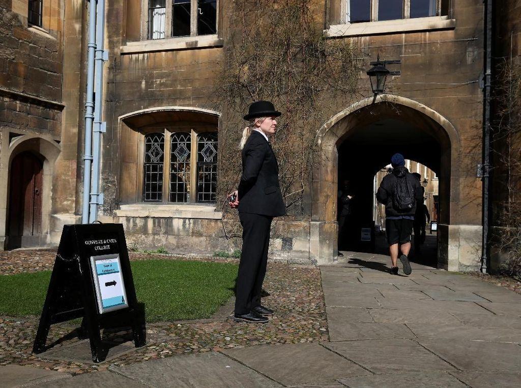 Seorang petugas bertugas mengarahkan mahasiswa yang hendak menulis ucapan dukacita untuk meninggalnya Stephen Hawking (Foto: REUTERS/Chris Radburn)