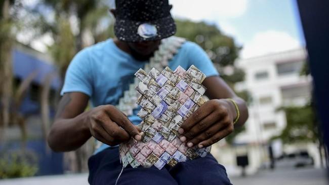 Wilmer Rojas (25) memungut uang kertas dari jalanan dan melipatnya dengan teknik serupa origami. (AFP Photo/Federico Parra)