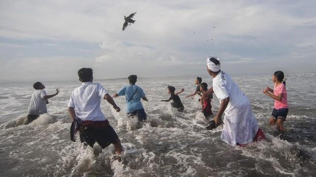 Tak hanya masyarakat yang tinggal di Bali, warga yang merantau sengaja pulang kampung dan melakukan Melasti dalam rangkaian Nyepi di Bali (ANTARA FOTO/Nyoman Budhiana)