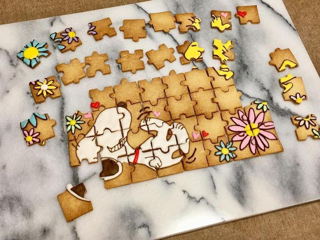 Ada banyak potongan puzzle! Kalau diacak pasti bingung yang mana yang bagian kue berlukis snoopy dan anak anjing berwarna kuning. Kreasi ini dibuat oleh pembuat kue asal Jepang. Foto: Instagram @serinaaa24