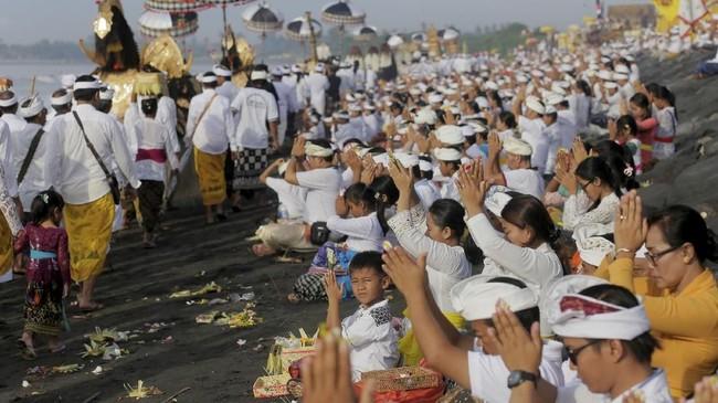 Iring-iringan masyarakat yang mengarak benda-benda sakral untuk disucikan dalam ritual Melasti menjadi pemandangan menarik bagi wisatawan yang datang ke Bali. (REUTERS/Johannes P. Christo)