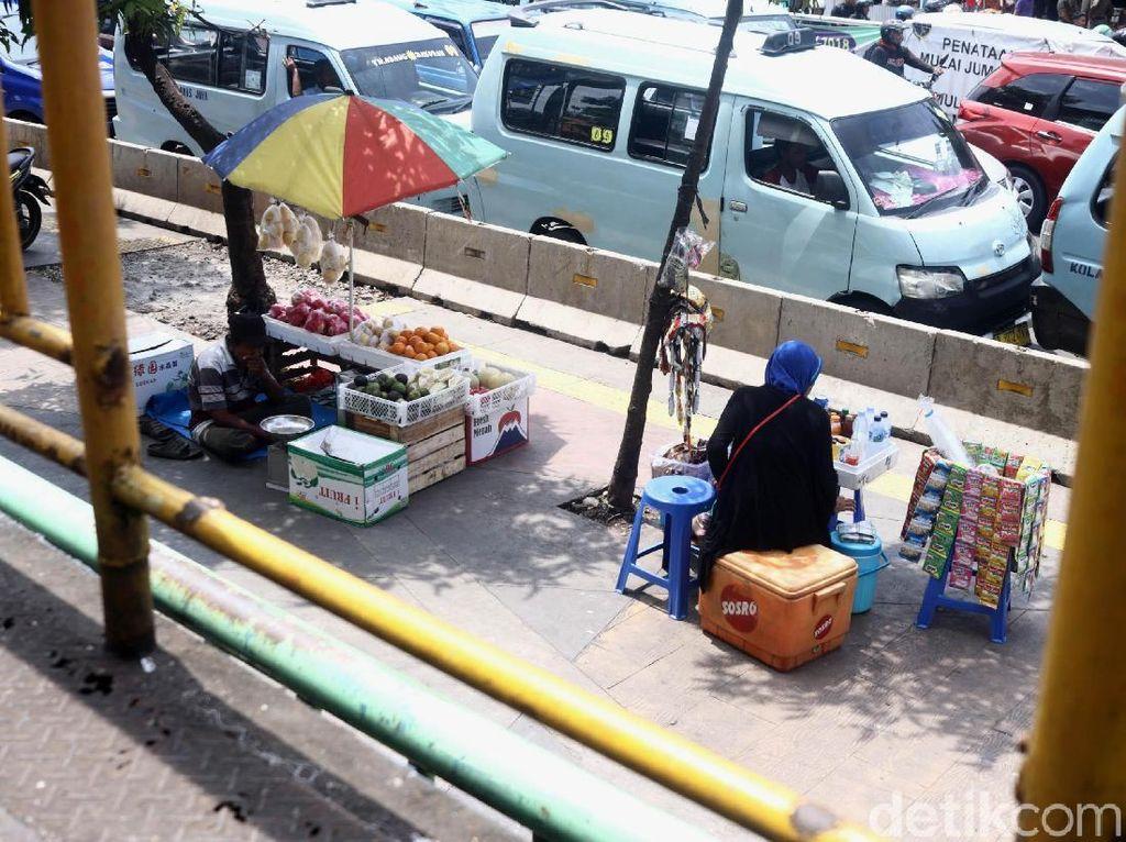 Mulai dari pedagang minuman hingga buah asyik berjualan di atas trotoar tersebut.