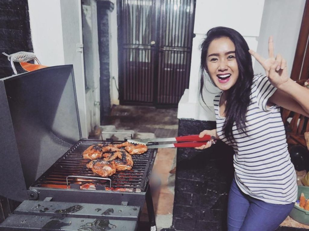 Meski sudah jadi penyanyi dangdut terkenal, Cita tidak takut terkena asap dari ayam bakar yang sedang dipanggangnya. Lengkap dengan pose senyuman dua jari darinya Foto: Instagram @cita_citata