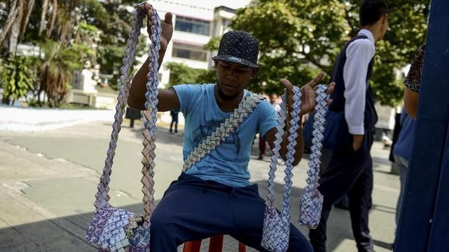 Dia bisa menggunakan 800 lembar uang untuk membuat sebuah tas jinjing, dan dengan nilai tukar yang sangat rendah jumlah itu hanya cukup dibelikan setengah kilogram beras. (AFP Photo/Federico Parra)