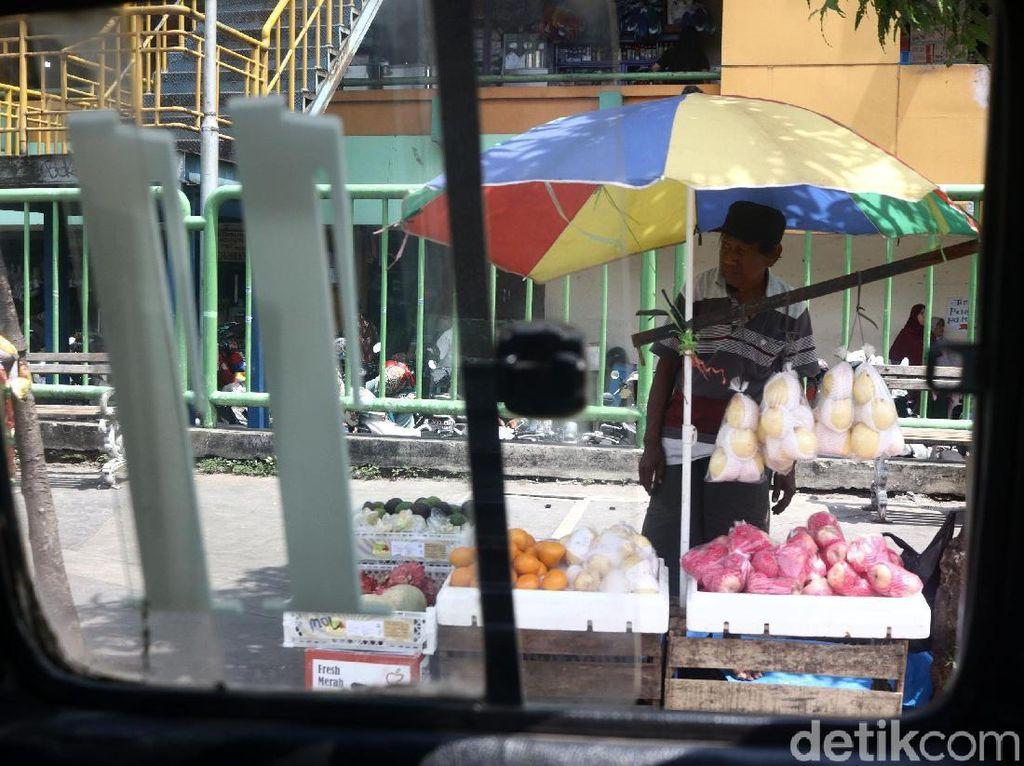 Pedagang menggelar dagangan di atas boks-boks. Mereka juga menbentangkan payung untuk melindungi diri dari sengatan sinar matahari.