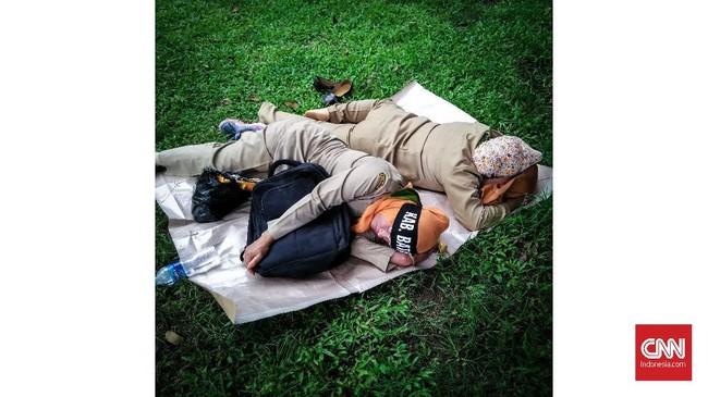 Dua pedemo merebahkan tubuh tidur di Taman Monas, Jakarta. Tidur yang berkualitas memiliki pengaruh besar pada kualitas kesehatan fisik dan mental. (CNNIndonesia/Safir Makki)
