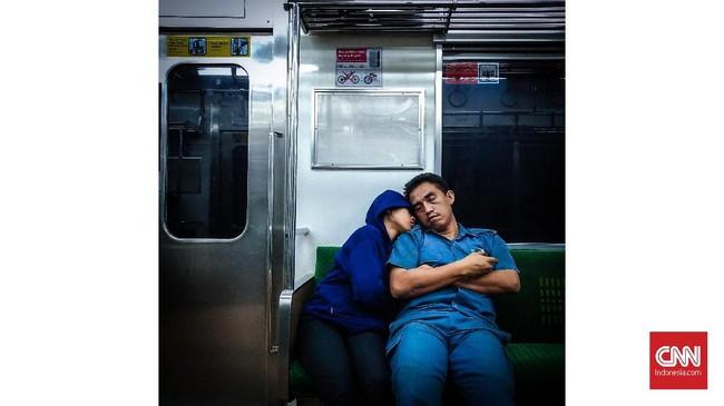 Dua penumpang terlelap tidur di commuterline Jakarta. Beban hidup, ragam aktivitas hingga perkembangan teknologi membuat masyarakat modern kian lama terjaga. (CNNIndonesia/Safir Makki)