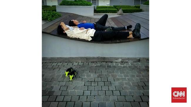 Pekerja tidur di taman perkantoran kawasan Jendral Sudirman, Jakarta. Di Indonesia, banyak kecelakaan lalu lintas yang merenggut korban jiwa dipacu oleh pengemudi yang mengantuk. Meskipun belum ada penelitian, kondisi masyarakat yang mudah marah dan emosi juga bisa disebabkan kurang tidur. (CNNIndonesia/Safir Makki.)