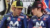 Duo Movistar Yamaha Valentino Rossi (kiri) dan Maverick Vinales berbicara sebelum sesi foto para pebalap MotoGP 2018 di Sirkuit Internasional Losail. (AFP PHOTO / KARIM JAAFAR)