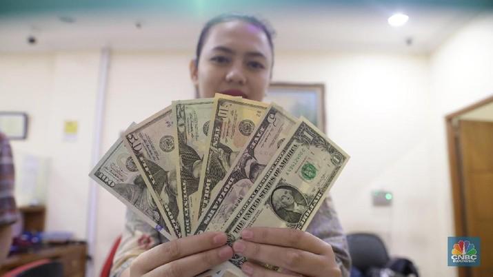 Karyawan menunjukkan pecahan uang dollar di salah satu tempat penukaran uang di kawasan Blok M, Kebayoran Baru, Jumat (16/3/2018). (CNBC Indonesia/Muhammad Sabki)