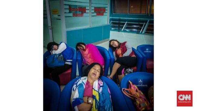 Calon penumpang tertidur pulas sembari menunggu keberangkatan pesawat di Bandara Soekarno Hatta, Banten. Kurangnya waktu tidur tidak hanya berdampak pada kesehatan fisik dan mental jangka pendek dan panjang, tetapi dapat membebani ekonomi. (CNNIndonesia/Safir Makki)