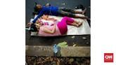 Warga memanfaatkan jalan yang tak berfungsi untuk tidur siang di kawasan Menteng, Jakarta. World Sleep Society dalam peringatan Hari Tidur Sedunia 2018 menyebutkan, 45 persen warga dunia punya masalah tidur. Sebanyak 35 persen penduduk bumi tak punya waktu tidur yang cukup 7-8 jam sehari untuk orang dewasa. (CNNIndonesia/Safir Makki)