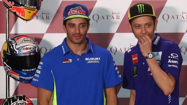 Valentino Rossi berpose bersama Andrea Iannone. Rossi melakukan perpanjangan kontrak dengan Movistar Yamaha hingga 2020 beberapa jam sebelum konferensi pers MotoGP Qatar. (AFP PHOTO / KARIM JAAFAR)