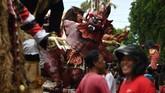 Wisatawan dan masyarakat sekitar menyaksikan parade Ogoh-Ogoh jelang Hari Raya Nyepi di Denpasar, Bali. Hari Raya Nyepi sendiri digelar hari ini, Sabtu (17/3). (AFP PHOTO / Sonny Tumbelaka)
