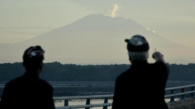 Pecalang atau petugas pengamanan adat Bali memantau situasi dengan latar belakang Gunung Agung yang mengeluarkan asap saat Hari Raya Nyepi tahun Caka 1940 di Jalan Tol Bali Mandara, Badung, Bali, Sabtu (17/3). (ANTARA FOTO/Fikri Yusuf)