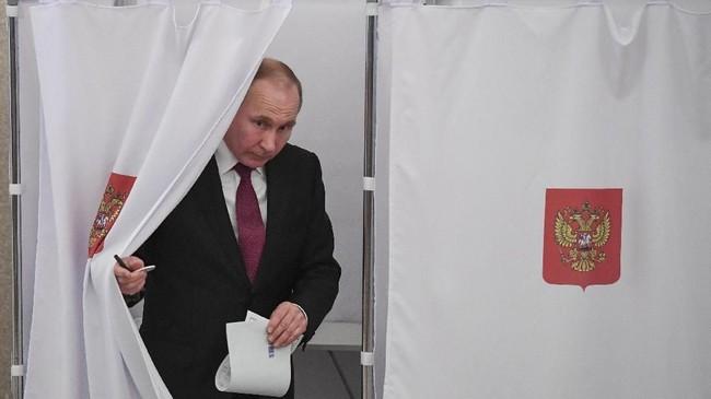 Vladimir Putin keluar dari bilik suara. Ini adalah kali keempat dia ikut dalam proses pemilihan presiden. (Yuri Kadobnov/POOL via Reuters)