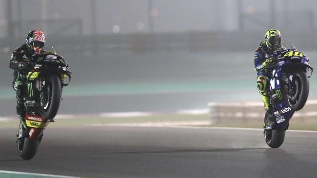 Pebalap Tech3 Yamaha Johann Zarco (kiri) dan pebalap Movistar Yamaha Valentino Rossi melakukan wheelie usai babak kualifikasi MotoGP Qatar. (AFP PHOTO / KARIM JAAFAR)