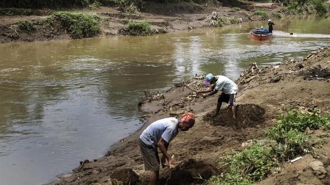 Di tengah kepungan limbah beracun, warga mencari pasir di bantaran Sungai Citarum di Desa Parigi, Ciparay, Bandung, Jawa Barat.(Anadolu Agency/Eko Siswono)