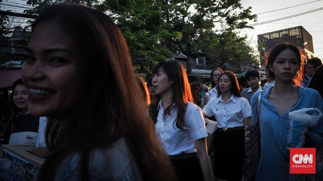 Mengeksplorasi cahaya adalah bagian dari fotografi jalanan. Cahaya matahari sore membias pada rambut pejalan di pasar akhir pekan Chatuchak. Pilihlah waktu yang pas menekan rana kamera, tekan rana secaracontinue untuk menemukan frame dan komposisi yang pas.