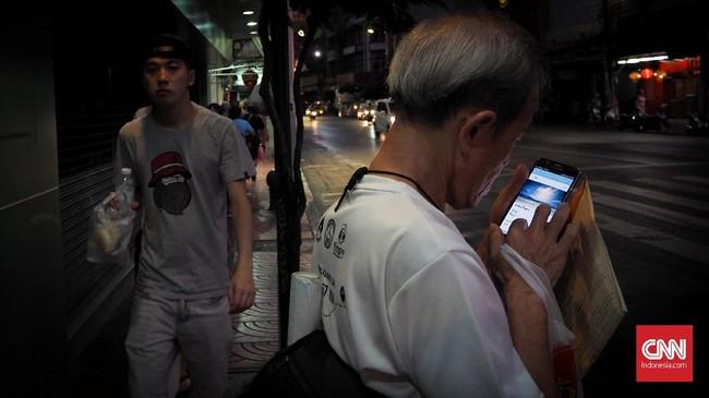 Dua pejalan kaki laki-laki muda dan tua di kawasan Yaowarat Pecinan Bangkok membentuk teknis juxtaposition. (berlawanan).
