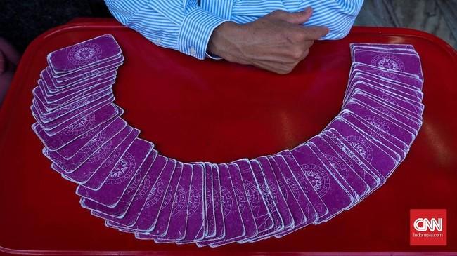 Peramal dengan kartu tarot yang disusun membentuk setengah lingkaran di kawasan Pasar Khlong Toei Bangkok. Memotret dengan gaya fotografi jalanan tak selalu menampilkan sosok penuh manusia. Elemen garis, lengkungan dan warna memberikan pesan visual yang beda.
