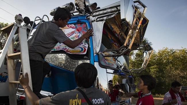 Truk-truk ini berukuran raksasa dan memiliki 20 roda. Tubuh truk dihiasi lukisan yang bervariasi mulai dari gambar unicorn hingga Transformers. Penampilan truk tak mungkin membuat kepala tak menoleh. (AFP PHOTO / LILLIAN SUWANRUMPHA)