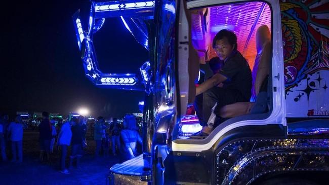 Seorang pengemudi duduk di dalam truknya yang dicat dengan desain khusus. Mengecat truk sendiri bisa membuat para pengemudi terhindar dari para pencuri bahan bakar. (AFP PHOTO / LILLIAN SUWANRUMPHA)