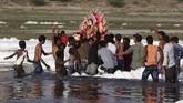 Sementara itu, patung besar Dewa Durga dilarung di sungai yang penuh busa itu. (REUTERS/Adnan Abidi)