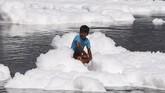 Apalagi itu diselenggarakan di berbagai sungai di India. Di New Delhi, festival itu digelar di Sungai Yamuna yang penuh polusi. Terlihat anak-anak bermain dengan busa. (REUTERS/Adnan Abidi)