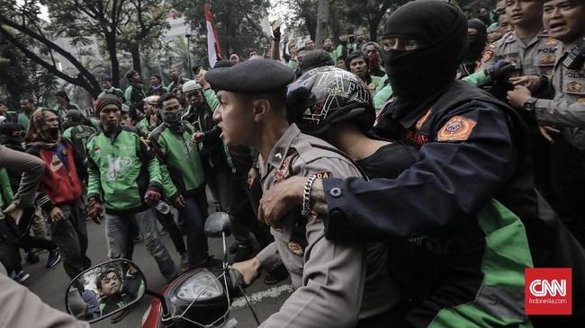 Di tengah aksi, sempat terjadi insiden. Peserta demo mengepung rekan mereka sesama pengemudi ojek yang tak ikut demo dan kedapatan membawa penumpang melewati peserta aksi. (CNN Indonesia/Adhi Wicaksono)