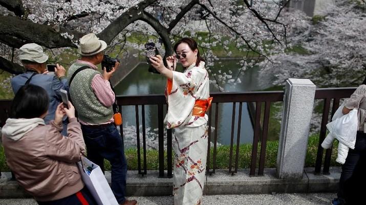 Seorang wanita berbaju kimono mengambil foto selfie di parit Chidorigafuchi, saat pengunjung menikmati bunga sakura yang mekar sepenuhnya, selama musim semi di Tokyo, Jepang 26 Maret 2018. REUTERS / Issei Kato