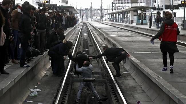 Di Stasiun Gare du Lyon, stasiun kereta api tersibuk di Paris, platform kereta sangat padat sehingga seorang wanita terjatuh ke rel dan dibantu berdiri oleh sesama penumpang. (REUTERS/Gonzalo Fuentes)