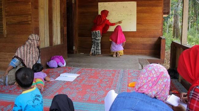 Nurma (35 tahun), sedang mengajari seorang ibu yang tidak bisa membaca, menulis, dan berhitung. Sejak 2010, Nurma yang hanya tamatan Sekolah Dasar menjadi guru bagi ibu-ibu di desa Melidi. Tercatat sebanyak 80 persen orang dewasa di Melidi tidak bisa membaca. (Anadolu Agency-Khalis Surry).