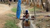 Seorang anak mandi di halaman rumahnya di Desa Melidi. Empat dari delapan desa yang terdapat di Kecamatan Simpang Jernih belum tersalurkan arus listrik dari PLN sejak daerah itu berdiri pada tahun 1919. (Anadolu Agency-Khalis Surry).