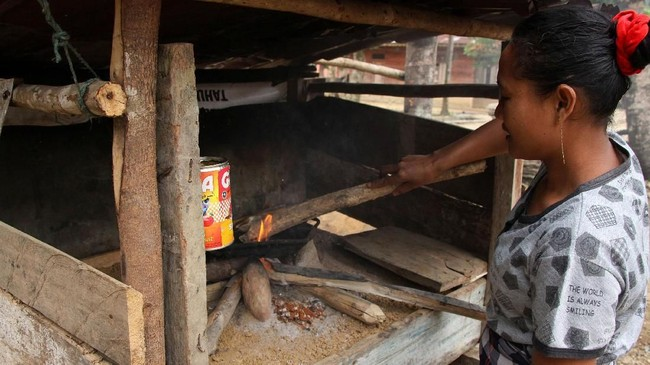 Seorang warga Desa Tampor Paloh, Kecamatan Simpang Jernih menyalakan api di tungku guna memasak nasi menjelang malam hari. (Anadolu Agency-Khalis Surry).