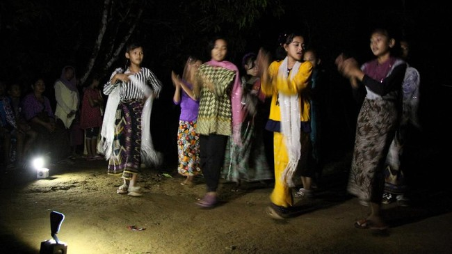 Anak perempuan di Desa Melidi sedang latihan tarian Bines dalam kondisi gelap gulita, hanya dibantu penerangan dari lampu baterai.(Anadolu Agency-Khalis Surry).