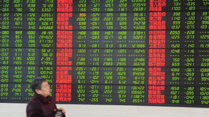 A woman walks past an electronic board showing stock information at a brokerage house in Fuyang, Anhui province, China March 23, 2018. China Daily via REUTERS   ATTENTION EDITORS - THIS IMAGE WAS PROVIDED BY A THIRD PARTY. CHINA OUT.