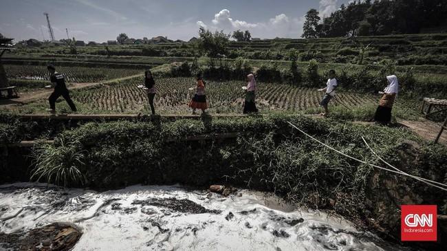 Warga melintasi di sekitar sungai Cikacembang yang merupakan anak sungai Citarum, Sabtu (31/3). Buih busa dan bau menyengat menjadi pemandangan sehari-hari warga sekitar.(CNNIndonesia/Adhi Wicaksono).