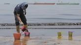 Petugas membersihkan Pantai Banua Patra dari minyak yang memenuhi pesisir pantai di Balikpapan, Kaltim, Senin (2/4). Pasca kebakaran pipa minyak bawah air Balikpapan-Penajam Paser Utara, pesisir pantai dan pemukiman di pinggir laut Kota Balikpapan tercemar tumpahan minyak. (ANTARA FOTO/Sheravim)