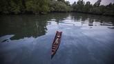 Perahu mengapung di atas air berwarna hitam karena terkontaminasi tumpahan minyak di hutan bakau di desa Kariangau, Teluk Balikpapan, Kalimantan Timur. Tumpahan minyak disebabkankebocoran dari pipa minyak Pertamina. (Greenpeace / Jurnasyanto Sukarno)