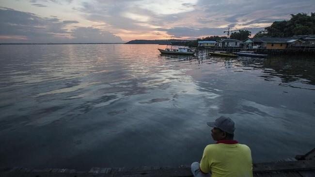 Seorang lelaki duduk di dermaga di atas perairan terkontaminasi oleh tumpahan minyak di desa Kariangau, Teluk Balikpapan, Kalimantan Timur. (Greenpeace / Jurnasyanto Sukarno)