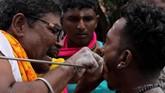Pengarakan arca itu merupakan momen sakral yang menandakan penghormatan terhadap Dewa Muruga. Saat itu pula ada ritual ekstrem. Para umat Hindu menusuk kening, pipi serta badan mereka dengan jarum dan busur panah besi. (Khalis Surry - Anadolu Agency)