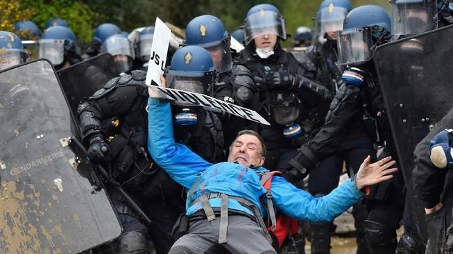Pada siang harinya, polisi menyatakan 10 dari 97 penghuni ilegal dilumpuhkan dan satu orang ditahan karena melempar bom. (AFP Photo/Loic Venance)