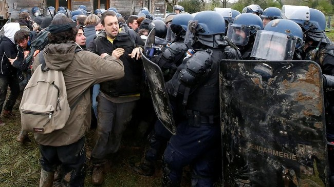 Bentrokan pun tak terhindarkan. Tak hanya itu, demonstran membuat barikade api dan melempar polisi dengan bom molotov. (REUTERS/Stephane Mahe)