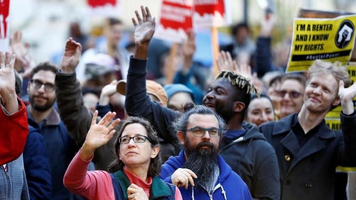 Orang-orang melambai kepada karyawan Amazon menyaksikan protes mereka di depan Amazon Sphere untuk menuntut bahwa kota Seattle mengenakan pajak kepada perusahaan-perusahaan terbesar untuk membantu mendanai perumahan yang terjangkau, menurut penyelenggara, di Seattle, Washington, AS, 10 April 2018. REUTERS / Lindsey Wasson