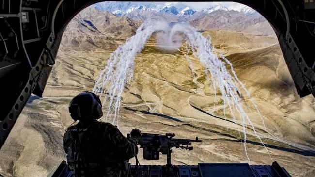 Dari atas helikopter CH-47F Chinook seorang tentara AS membidik sasaran dalam latihan perang di Afghanistan, 14 Maret 2018. (US Air Force/Tech. Sgt. Gregory Brook/Handout via REUTERS)