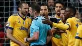 Menjelang laga berakhir pemain Juventus mengerumuni wasit Michael Oliver karena menunjuk titik putih di menit-menit akhir pertandingan setelah menilai Mehdi Benatia melanggar Lucas Vazquez. (REUTERS/Stringer)